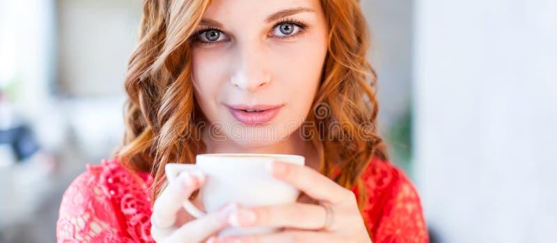 Una giovane bella donna sta bevendo il caffè in un caffè fotografia stock