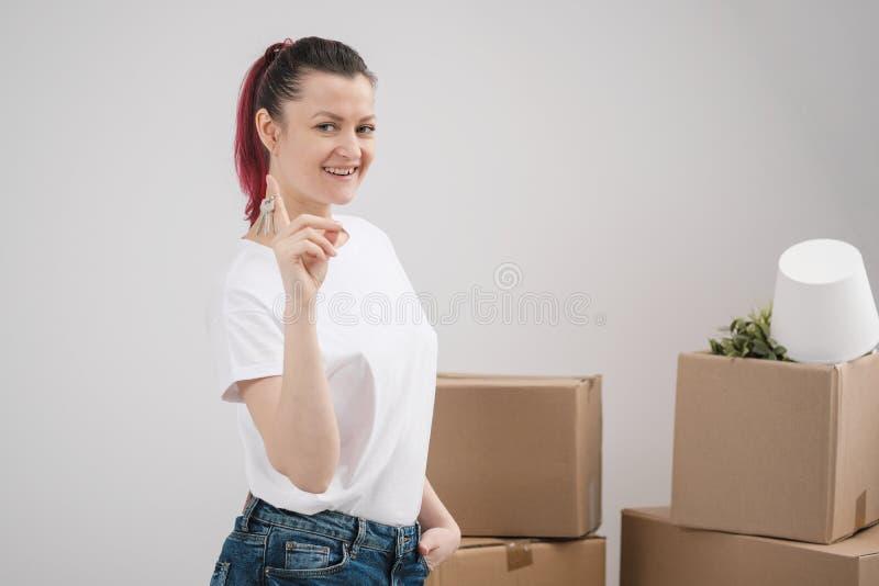 Una giovane bella ragazza castana in una maglietta bianca tiene in sue mani le chiavi ad una nuova casa, contro lo sfondo di fotografie stock