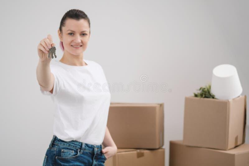 Una giovane bella ragazza castana in una maglietta bianca tiene in sue mani le chiavi ad una nuova casa, contro lo sfondo di immagini stock libere da diritti