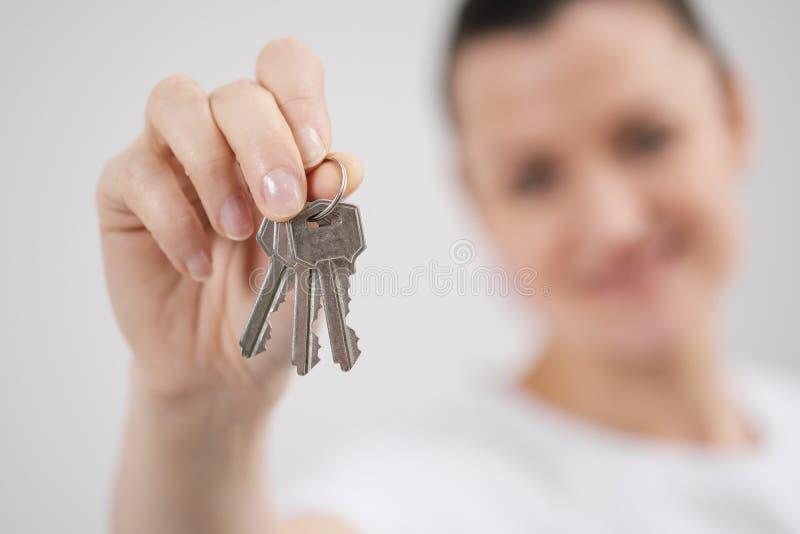 Una giovane bella ragazza castana in una maglietta bianca tiene in sue mani le chiavi ad una nuova casa, contro lo sfondo di fotografia stock