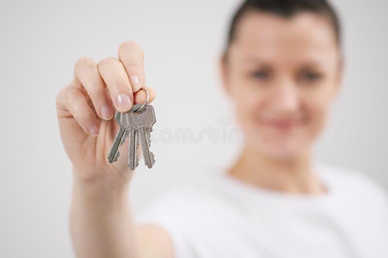 Una giovane bella ragazza castana in una maglietta bianca tiene in sue mani le chiavi ad una nuova casa, contro lo sfondo di fotografia stock libera da diritti