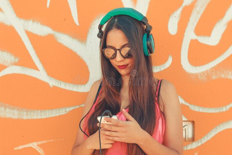 Una giovane bella ragazza ed il suo telefono cellulare da ascoltare musica in sue cuffie immagine stock libera da diritti