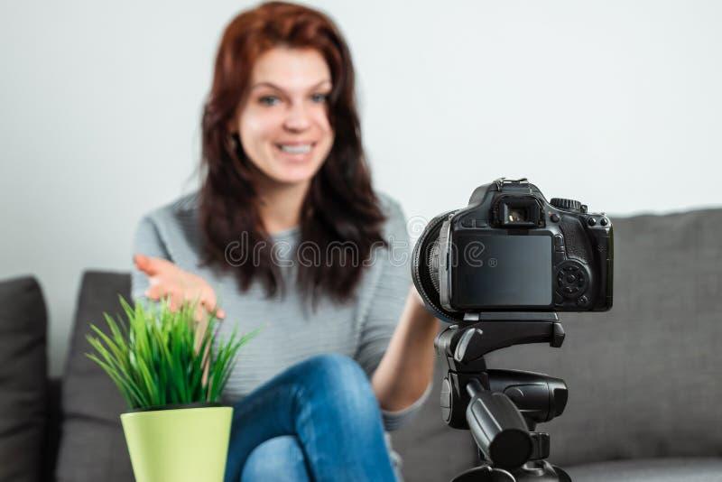 Una giovane bella ragazza sta sedendosi davanti ad un DSLR e ad una a di registrazione Vlog, primo piano Blogger, blogging, tecno fotografie stock