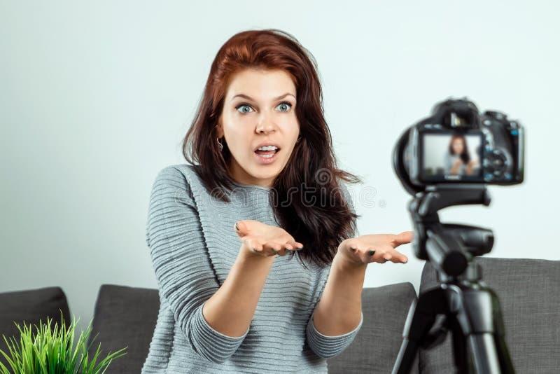 Una giovane bella ragazza sta sedendosi davanti ad un DSLR e ad una a di registrazione Vlog, primo piano Blogger, blogging, tecno immagine stock