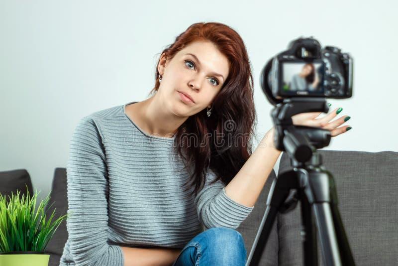 Una giovane bella ragazza sta sedendosi davanti ad un DSLR e ad una a di registrazione Vlog, primo piano Blogger, blogging, tecno immagini stock