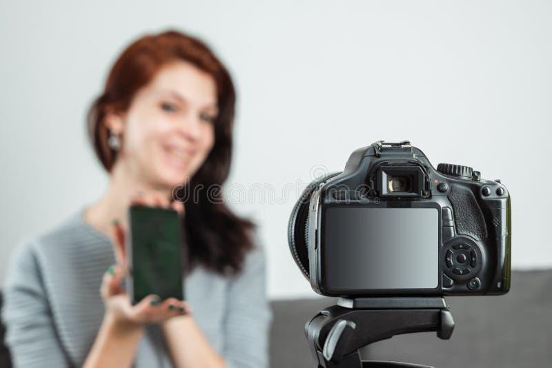 Una giovane bella ragazza sta sedendosi davanti ad un DSLR e ad una a di registrazione Vlog, primo piano Blogger, blogging, tecno immagini stock libere da diritti