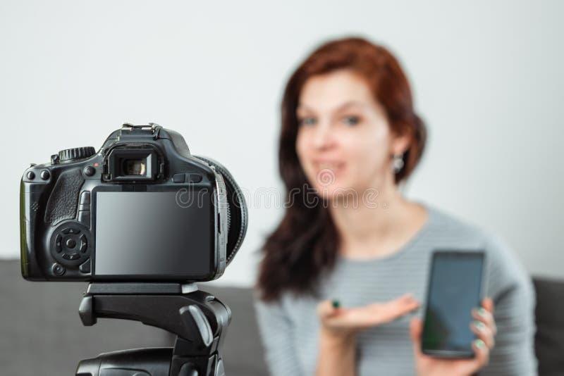 Una giovane bella ragazza sta sedendosi davanti ad un DSLR e ad una a di registrazione Vlog, primo piano Blogger, blogging, tecno fotografia stock libera da diritti