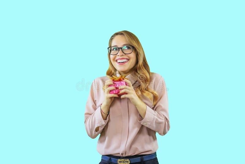 Una giovane bella ragazza tiene un piccolo regalo è deliziata e distoglie lo sguardo con un ampio sorriso su un fondo isolato blu immagini stock