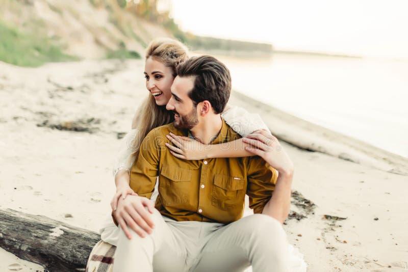 Una giovane coppia è divertentesi ed abbracciante sulla spiaggia La bella ragazza abbraccia il suo ragazzo dalla parte posteriore fotografia stock libera da diritti