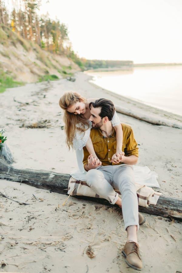 Una giovane coppia è divertentesi ed abbracciante sulla spiaggia La bella ragazza abbraccia il suo ragazzo dalla parte posteriore fotografie stock libere da diritti