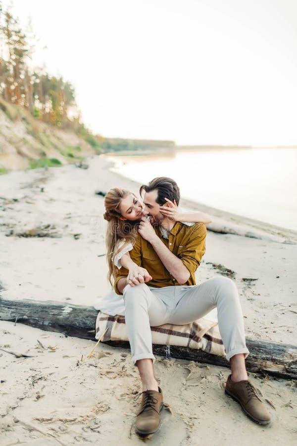 Una giovane coppia è divertentesi ed abbracciante sulla spiaggia La bella ragazza abbraccia il suo ragazzo dalla parte posteriore fotografia stock