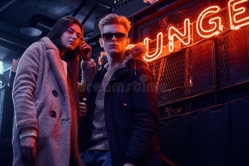 Una giovane coppia alla moda che indossa i vestiti caldi che stanno nel caffè con l'interno industriale, un'insegna retroillumina fotografia stock