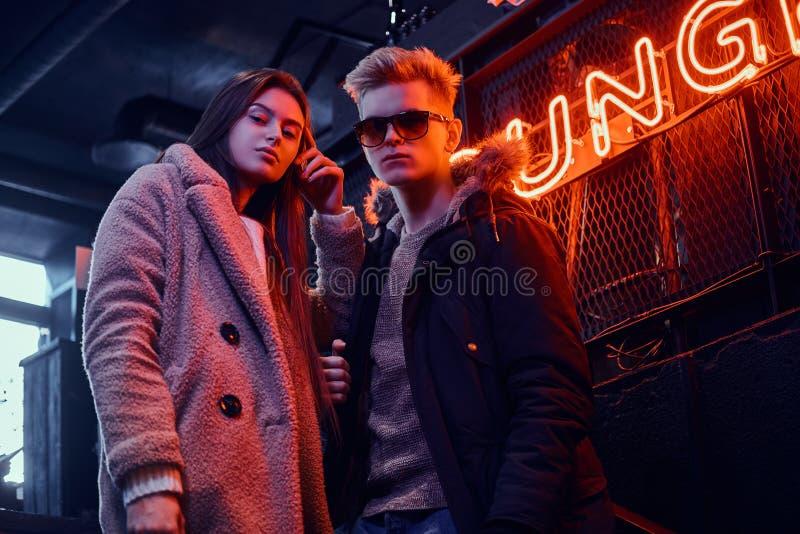 Una giovane coppia alla moda che indossa i vestiti caldi che stanno nel caffè con l'interno industriale, un'insegna retroillumina fotografia stock libera da diritti