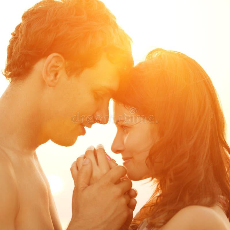 Una giovane coppia amorosa che abbraccia e che bacia sulla spiaggia ai soli fotografie stock libere da diritti
