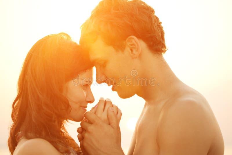 Una giovane coppia amorosa che abbraccia e che bacia sulla spiaggia al tramonto fotografie stock libere da diritti