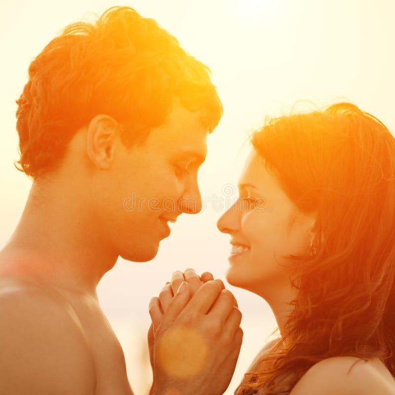 Una giovane coppia amorosa che abbraccia e che bacia sulla spiaggia al tramonto fotografia stock