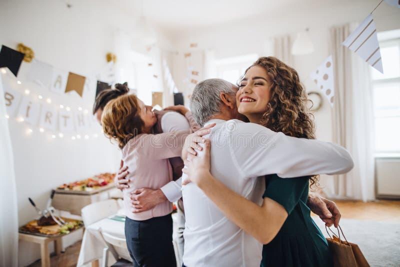 Una giovane coppia che accoglie i genitori o i nonni sulla festa di compleanno dell'interno fotografia stock