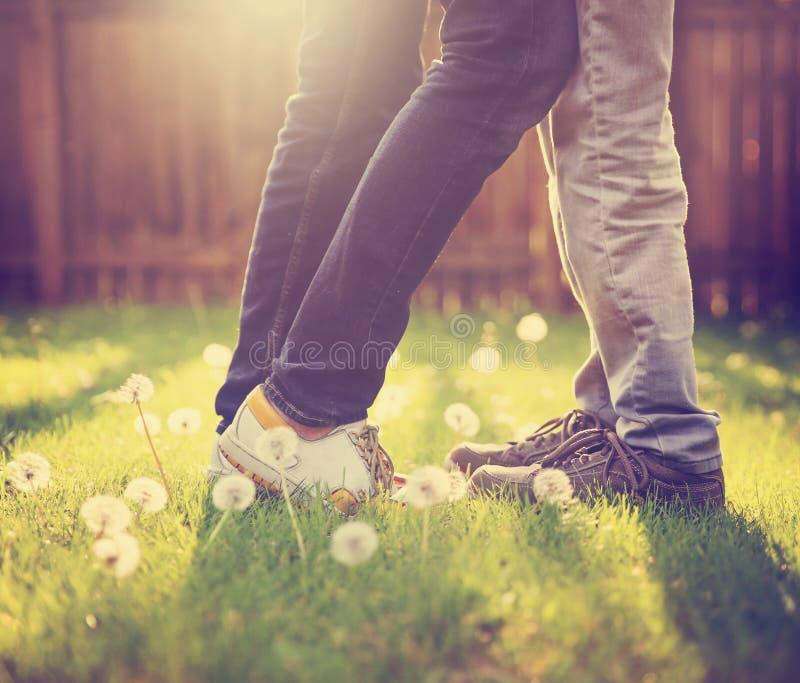 Una giovane coppia che bacia in un cortile di estate espone al sole la luce durante immagine stock libera da diritti
