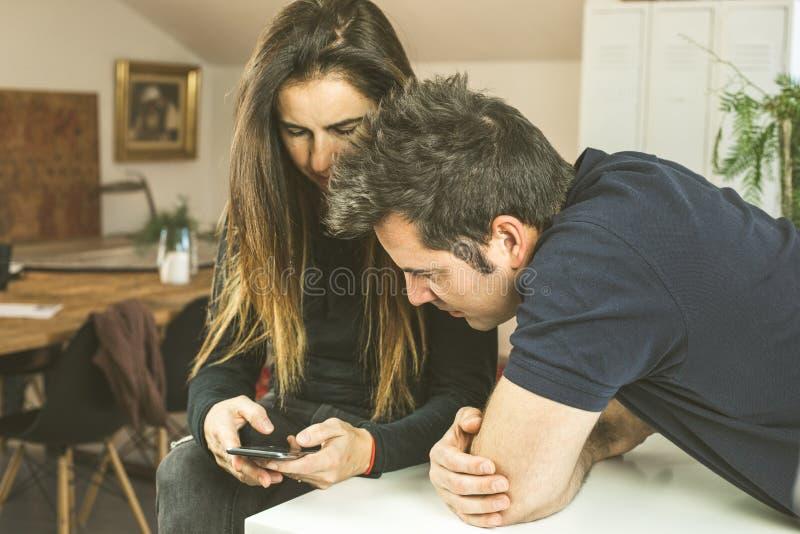 Una giovane coppia che esamina il telefono cellulare nella cucina Concetto di tecnologia immagine stock