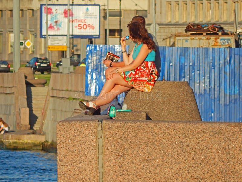 Una giovane coppia che si siede sul parapetto dell'argine del fiume di Neva nella città di San Pietroburgo, Russia immagini stock libere da diritti