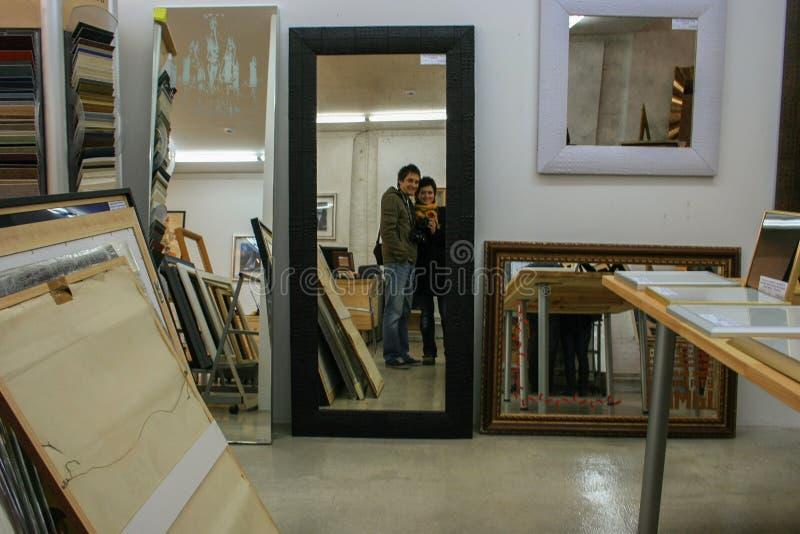 Una giovane coppia che si spara nello specchio Specchio nella stanza fotografia stock libera da diritti