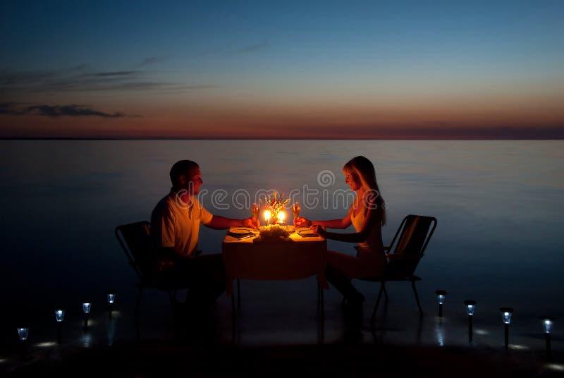Una giovane coppia divide un pranzo romantico con le candele sulla spiaggia fotografie stock