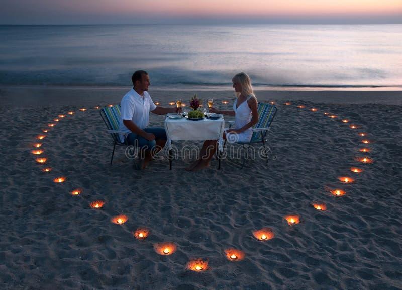 Una giovane coppia divide un pranzo romantico sulla spiaggia fotografia stock