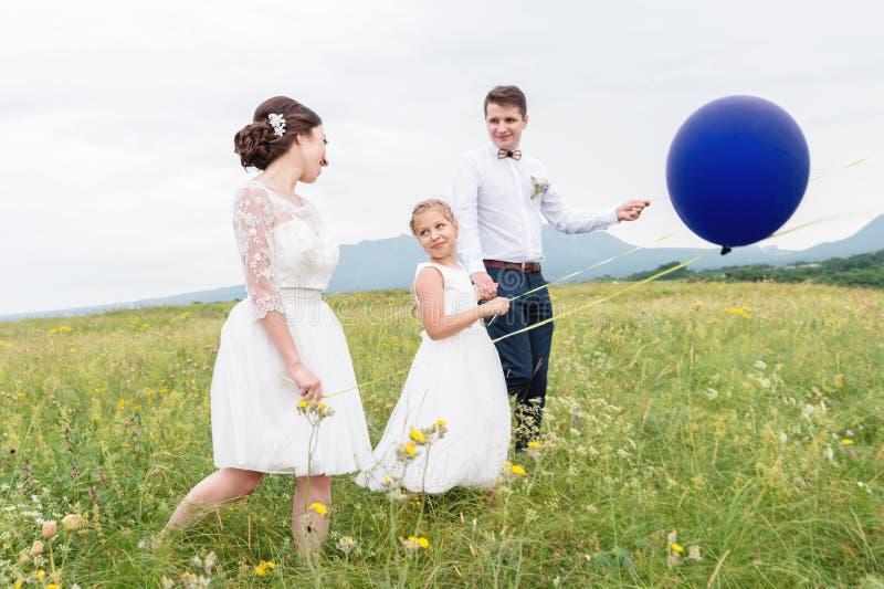 Una giovane coppia e la loro figlia in vestiti da sposa stanno camminando in natura con i palloni immagini stock