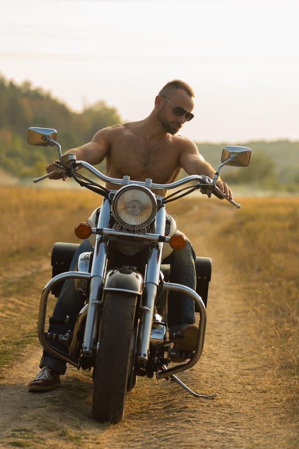 Una giovane coppia nell'amore su un motociclo nel campo fotografie stock libere da diritti