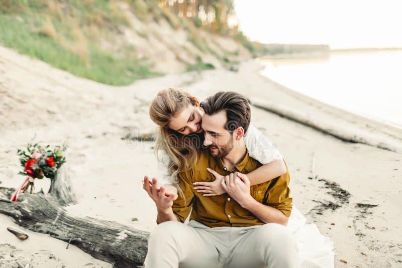 Una giovane coppia sta abbracciando sulla spiaggia La bella ragazza abbraccia il suo ragazzo dalla parte posteriore Camminata Wed fotografie stock