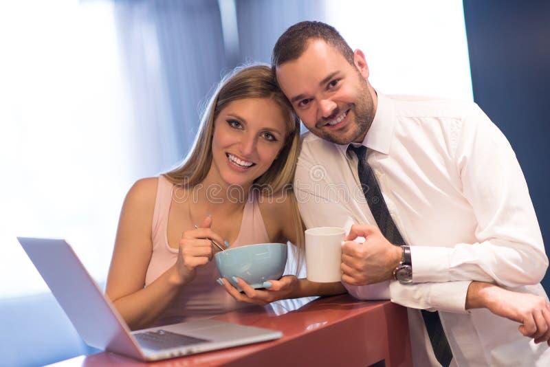 Una giovane coppia sta preparando per un lavoro e sta utilizzando un computer portatile immagine stock libera da diritti