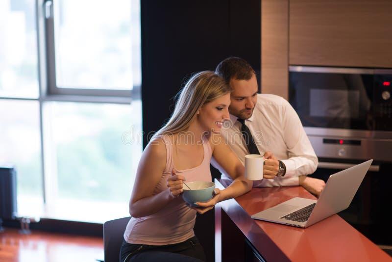 Una giovane coppia sta preparando per un lavoro e sta utilizzando un computer portatile fotografie stock