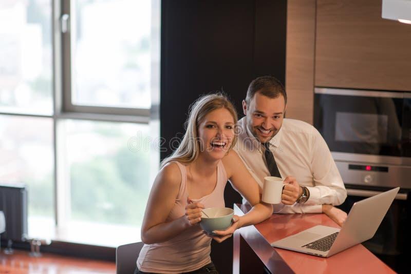 Una giovane coppia sta preparando per un lavoro e sta utilizzando un computer portatile fotografia stock