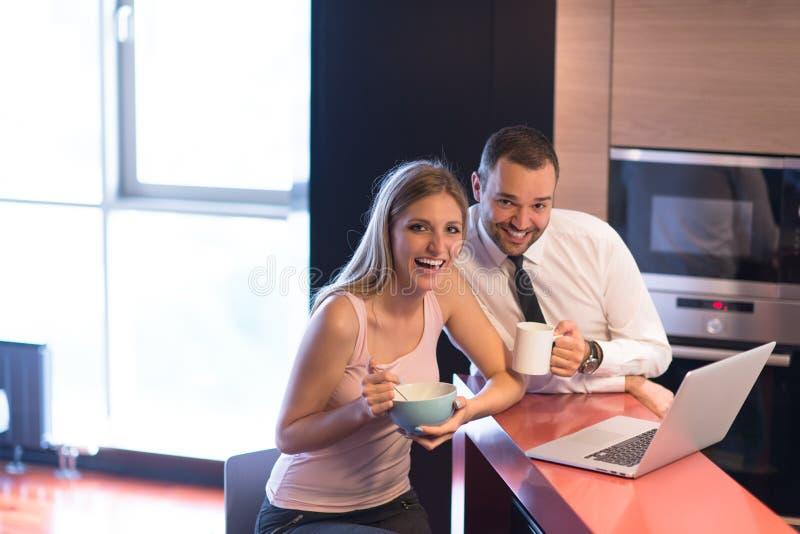 Una giovane coppia sta preparando per un lavoro e sta utilizzando un computer portatile immagini stock
