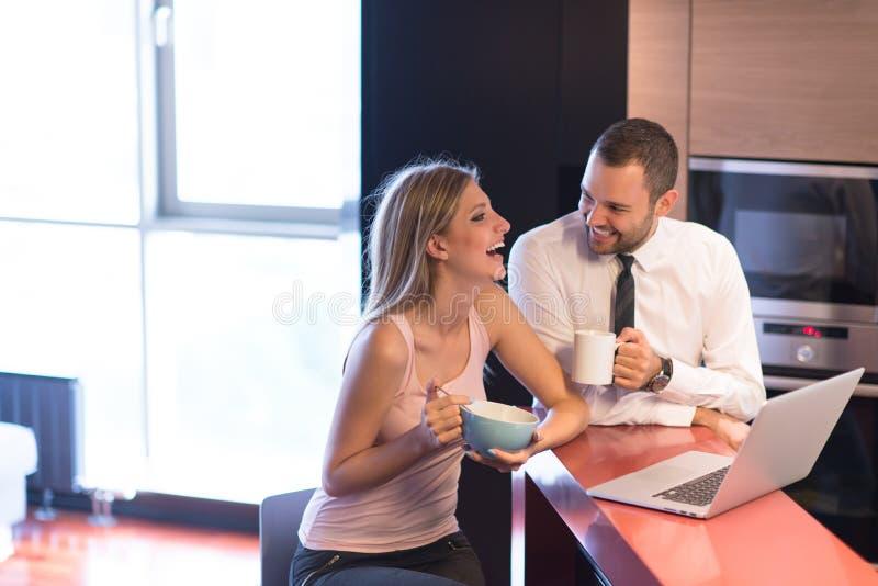 Una giovane coppia sta preparando per un lavoro e sta utilizzando un computer portatile immagini stock libere da diritti