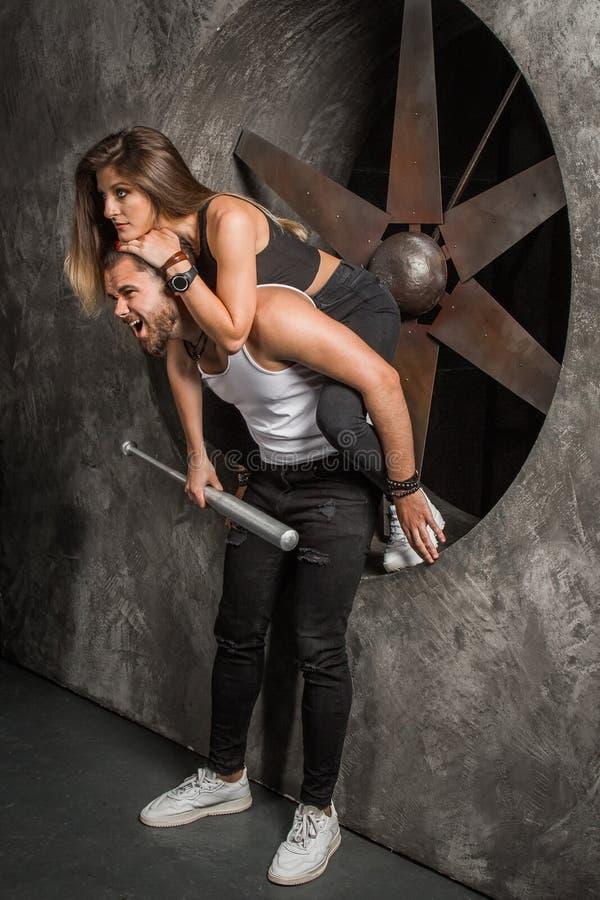 Una giovane coppia un uomo e una donna con uno sguardo alla moda e sportivo allegro dell'umore, si siede vicino ad un ventilatore fotografia stock