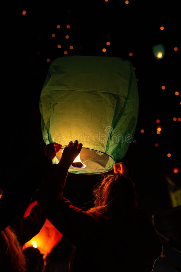 Una giovane donna è profilata mentre tiene una lanterna di galleggiamento prima della liberazione per galleggiare su nel cielo co immagine stock libera da diritti