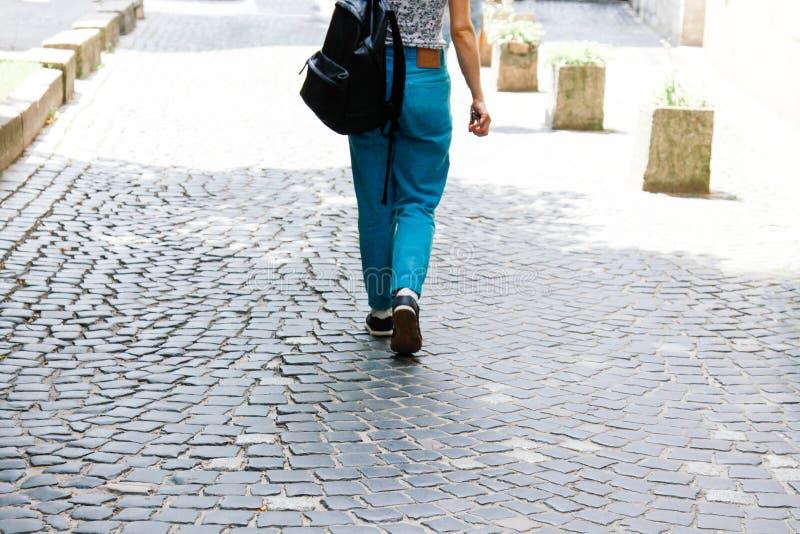 Una giovane donna in abbigliamento casual ed in uno zaino cammina giù la via Una donna guarda dalla parte posteriore Estate fotografie stock libere da diritti