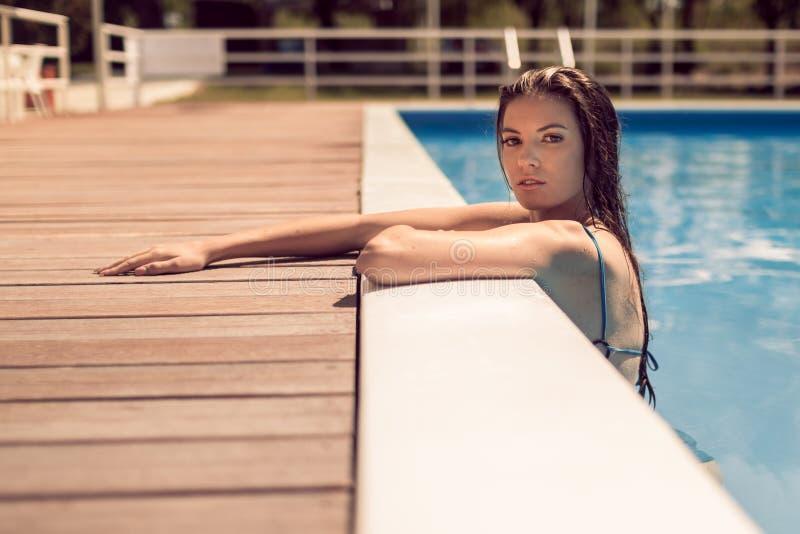Una giovane donna adulta, posando, bordo di rilassamento della piscina, insi immagine stock