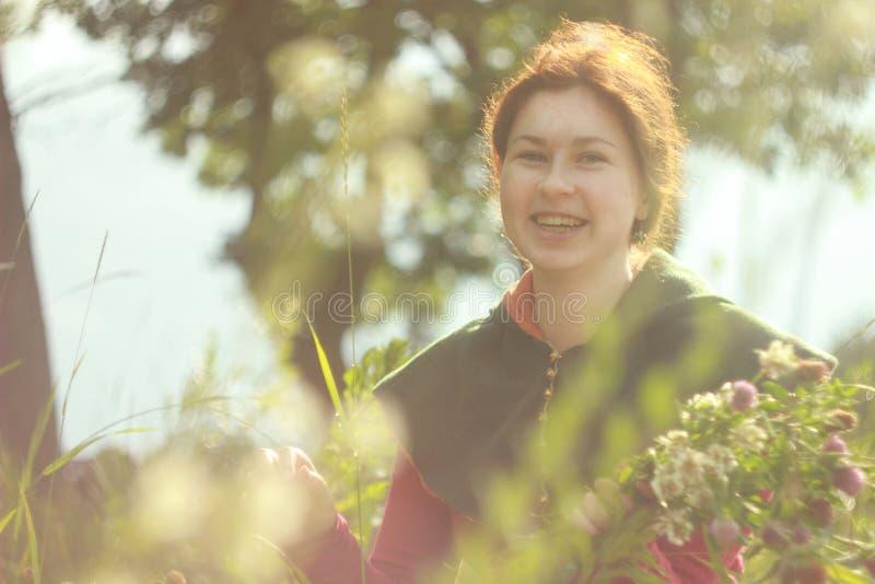 Una giovane donna bianca caucasica felice con capelli rossi lunghi è sorridente e ridente con un mazzo dei fiori in sue mani su u fotografie stock