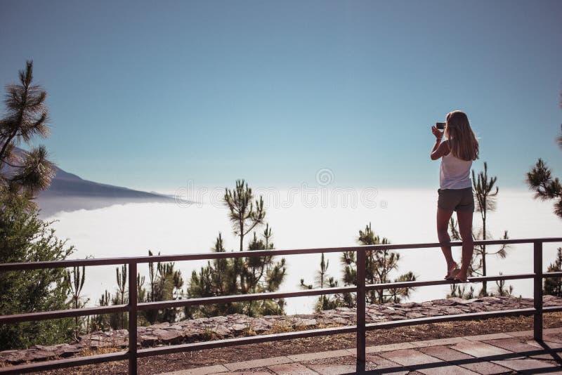 Una giovane donna bionda che resta sull'inferriata sulla collina sopra il cielo e che fa una foto dallo smartphone Sopra le monta fotografia stock