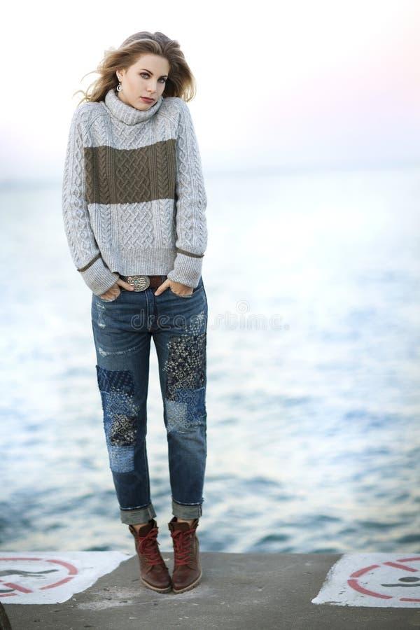 Una giovane donna bionda con capelli ricci su un pilastro del cemento accanto al lago Michigan fotografia stock