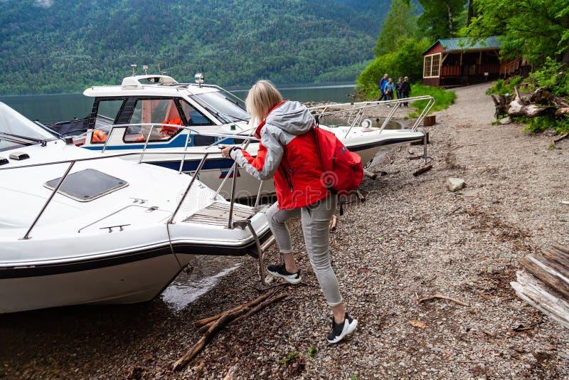 Una giovane donna bionda sale a bordo di una motoscafa su una scala per viaggiare lungo un fiume o un lago con un viaggio guidato immagine stock libera da diritti
