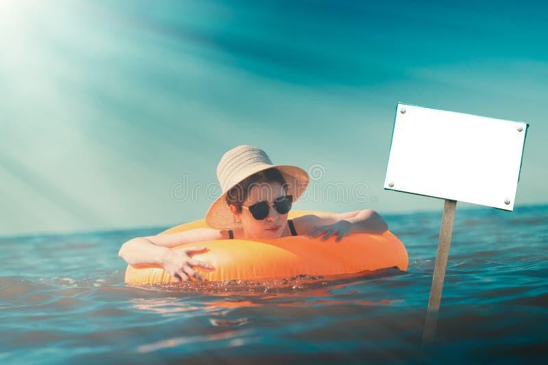 Una giovane donna in cappello, bagnante con un cerchio nel mare Sul fronte delle emozioni di timore e di panico Concetto di nuoto fotografia stock libera da diritti