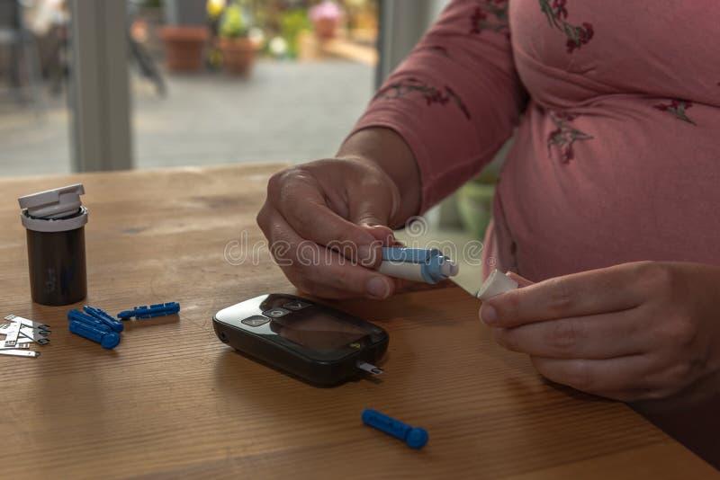 Una giovane donna a casa controlla il suo sangue immagine stock