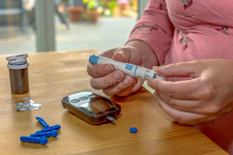 Una giovane donna a casa controlla il suo sangue fotografia stock