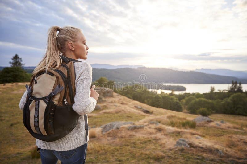 Una giovane donna caucasica adulta che sta da solo sulla collina durante l'escursione, vista piena d'ammirazione, vista posterior fotografia stock