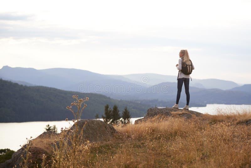 Una giovane donna caucasica adulta che sta da solo sulla roccia dopo l'escursione, vista piena d'ammirazione del lago, vista post immagini stock