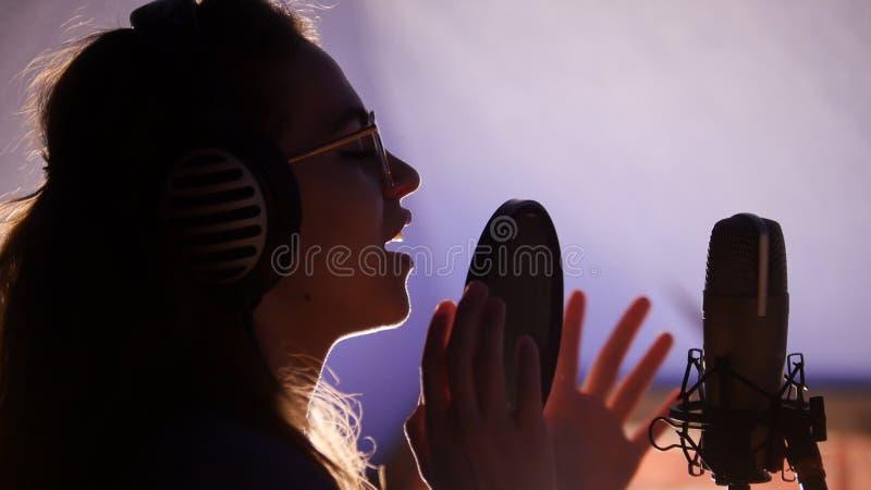 Una giovane donna che canta nello studio fotografia stock libera da diritti