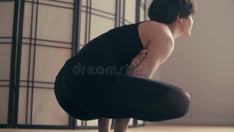 Una giovane donna che esegue yoga-asanas nel corridoio fotografia stock libera da diritti